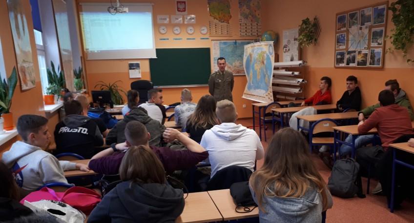 Grupa uczniów siedzących w szkolnych ławkach. Uczniowie słuchają przedstawiciela Wojskowej Komendy Uzupełnień ubranego w zielony mundur.