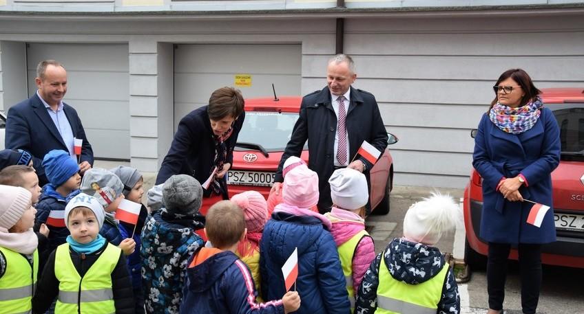 Grupa przedszkolaków odwiedza włodarzy Powiatu Szamotulskiego. Część uczestników spotkania trzyma flagi Polski. W tle budynki gospodarcze oraz zaparkowane auto.