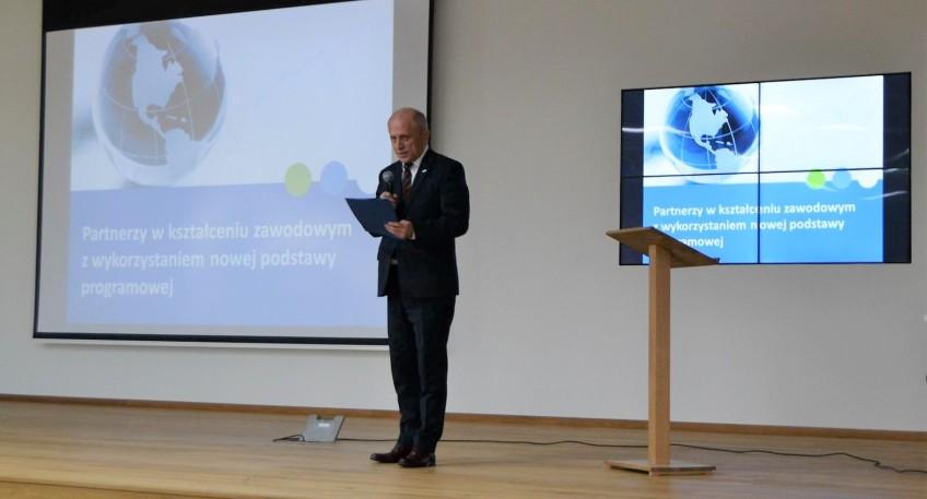 Wicekurator Oświaty dr Zbigniew Talaga przemawia na scenie. W tle widać dwie prezentacje.