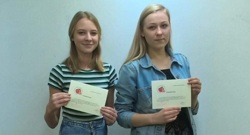 Dwie uśmiechnięte uczennice z szmotulskiej szkoły trzymające dyplom
