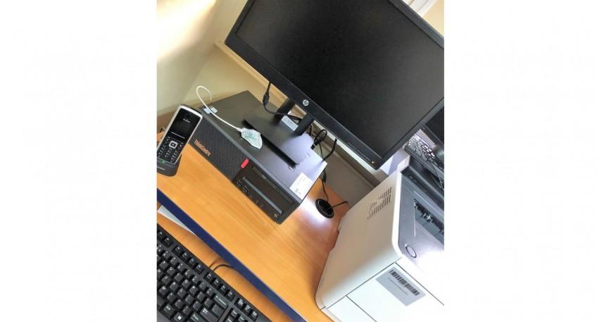 czarno-szary telefon stacjonarny, czarny komputer, czarny monitor, część czarnej klawiatury oraz biało-szara drukarka. Sprzęt stoi na drewnianym biurku.