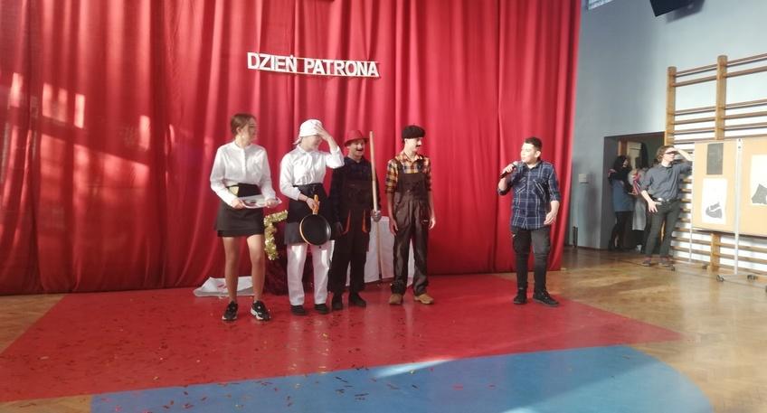 Pięciu uczniów grających w przedstawieniu. Uczniowie są przebrani. Z tyłu czerwona kotara z przyczepionym białym napisem