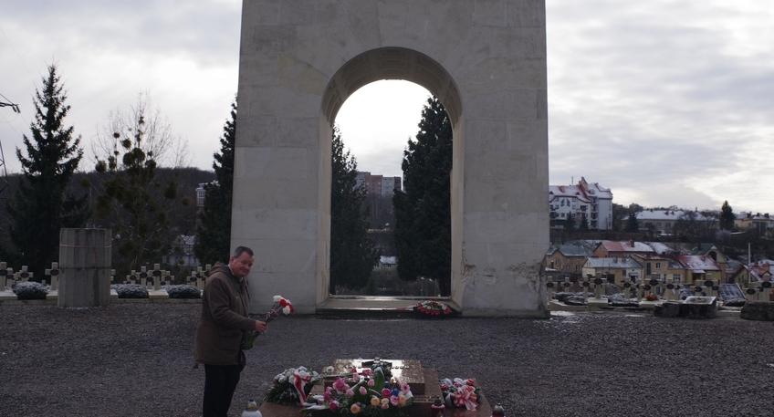 Zdjęcie przedstawia członka zarządu Powiatu Pana Macieja Trąbczyńskiego składającego bukiet biało-czerwonych kwiatów na cmentarzu.