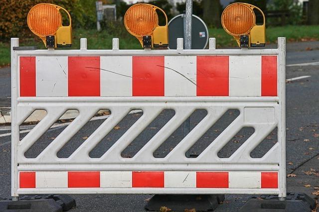 Zdjęcie przedstawia biało-czerwoną tymczasową barierę drogową. Na barierze znajdują się żółte sygnalizatory świetlne.