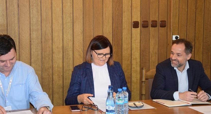 Zdjęcie przedstawia trzy osoby siedzące przy stole, z lewej strony Sekretarz Powiatu Pan Sławomir Masłowski, pośrodku Starosta Szamotulski Pani Beata Hanyżak, z prawej strony Wicestarosta Szamotulski Pan Rafał Zimny