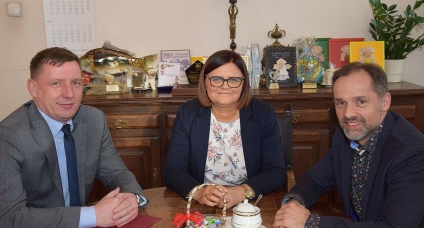 Zdjęcie przedstawia trzy osoby siedzące przy stole: z lewej strony Wicewojewoda Wielkopolski Pan Maciej Bieniek, na środku Starosta Szamotulski Pani Beata Hanyżak, a po prawej stronie Wicestarosta Szamotulski Pan Rafał Zimny.
