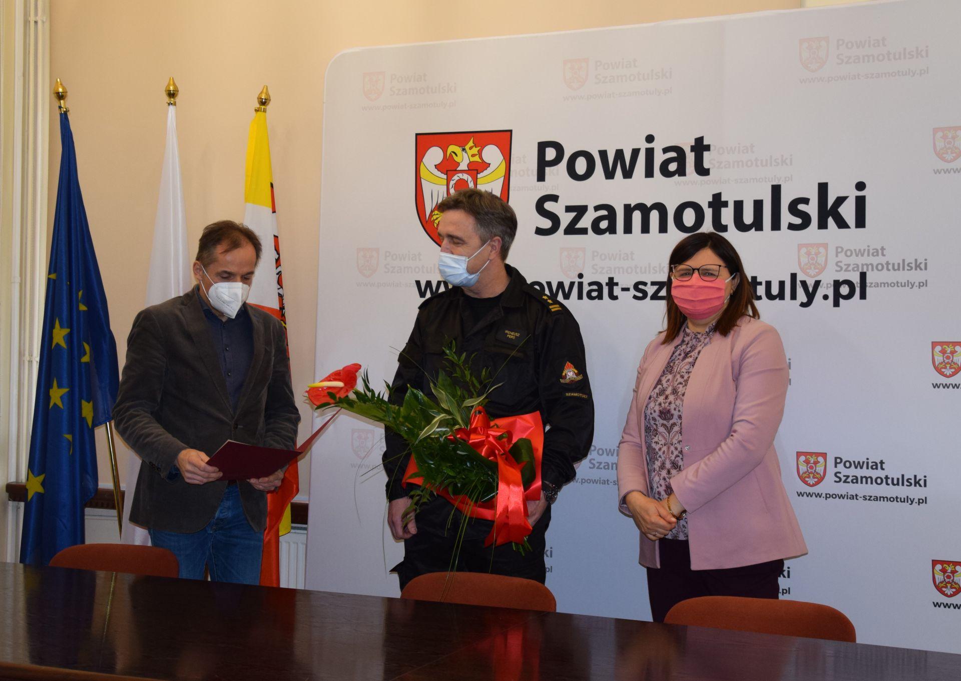 Starosta i Wicestarosta wręczają kwiaty na ręce Komendanta Powiatowej Straży Pożarnej